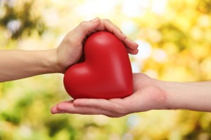 Red,Heart,In,Woman,And,Man,Hands,,On,Green,Background